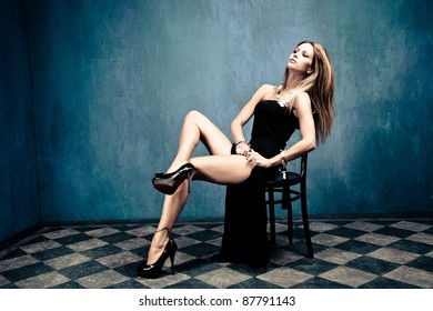 sensual blond in black dress and high heels sit on chair in empty room