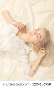 sensual blond girl in white blouse lying with closed eyes