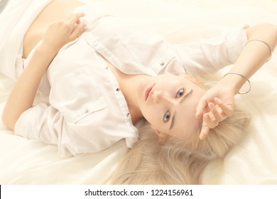 sensual blond girl in white blouse lying, looking at camera