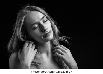 sensual blond transgender with closed eyes on black background