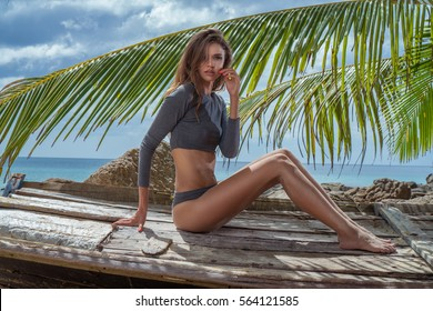 Sensual blond woman wearing gray long sleeve jumpsuit bodycon looking at the camera while sitting on the wooden boat over tropical island background