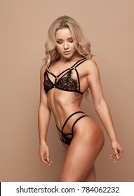 Sensual blonde beautiful woman posing in elegant black lingerie, looking at camera. Beige background. Studio shot.