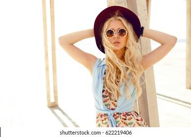 Sensual blonde girl with round sunglasses,denim shirt,cute dress,wave hair and burgundy hat ,enjoy the sunlight at sea.Horizontal view.