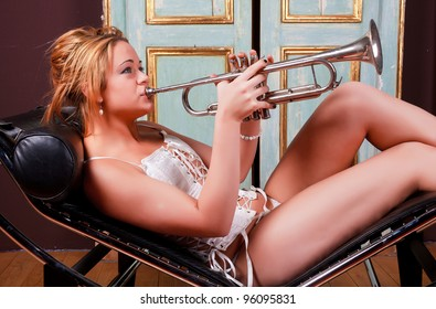 Sensual blonde girl in underwear playing trumpet on sceslong