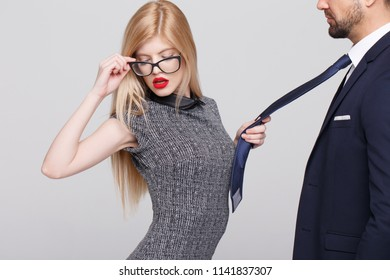 Sensual blonde manipulator woman pulling man by tie, closed eyes