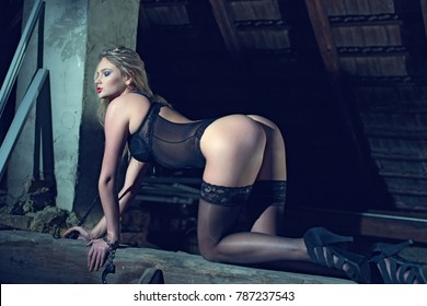 Sensual blonde woman kneeling on timber in barn, closed eyes, desire