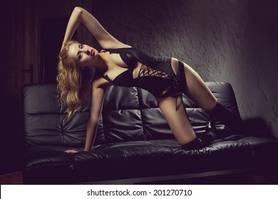 Sensual blonde woman with long hair lying on bed, posing in sexy lingerie