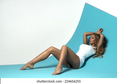 Sensual blonde woman with long hair lying on blue background in white shirt