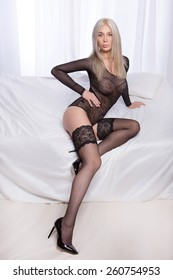 Sensual blonde woman lying on white bed , wearing black sexy lingerie, looking at camera.Girl with long hair.