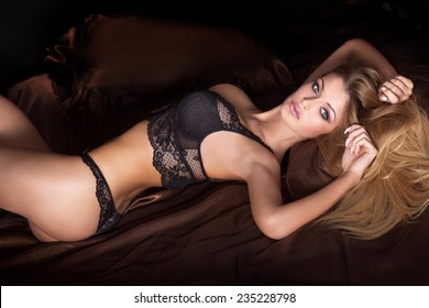 Sensual blonde woman posing in fashionable lingerie. Girl looking at camera. Studio shot.