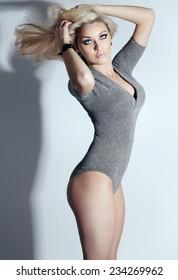 Sensual blonde woman posing in sexy pose. Indoor photo.