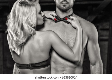 Sensual blonde woman straighten bow tie on naked sexy man, strippers at bachelor party, black and white, selective coloring