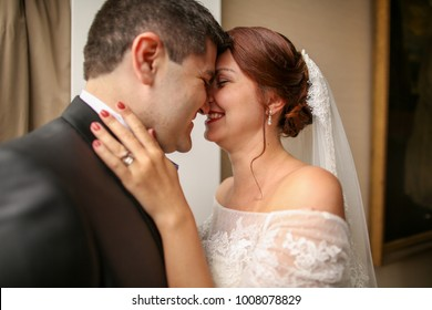 Sensual bride & groom hugging in hotel room, face closeup