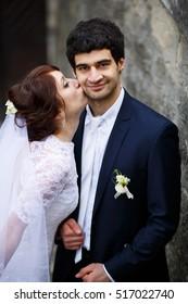 Sensual bride kissing handsome groom on his cheek