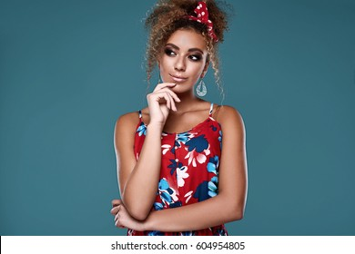 Sensual bright portrait of glamor elegant black woman model with curly hair in red dress posing on colorful background in studio