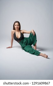 Sensual brunette female in green trousers and top with deep cleavage posing sitting on studio floor, looking at camera