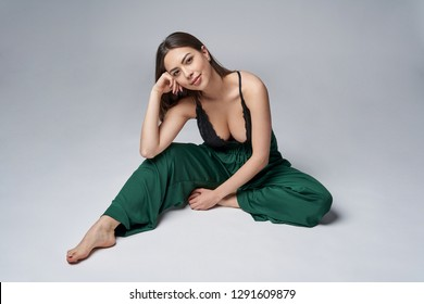 Sensual brunette female in green trousers and top with deep cleavage posing sitting on studio floor, smiling looking at camera
