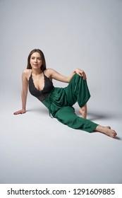 Sensual brunette female in green trousers and top with deep cleavage posing sitting on studio floor, looking away