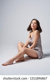 Sensual brunette female in satin night lingerie sitting on studio floor with closed eyes enjoying dreaming