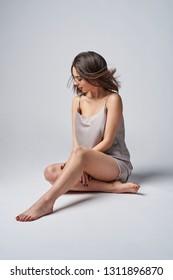 Sensual brunette female in satin night lingerie posing sitting on studio floor