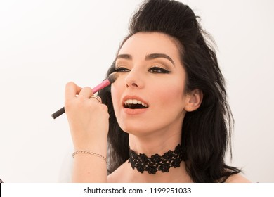 Sensual brunette model retro styled during makeup retouch on white background. Sophia Loren lookalike concept