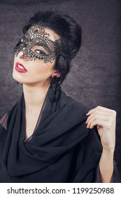Sensual brunette with retro look and black lace mask on black glowing background. The Great Gatsby Movie lookalike concept