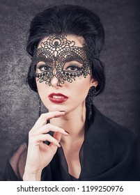 Sensual brunette with retro look and lace mask on black glowing background. The Great Gatsby Movie lookalike concept