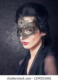 Sensual brunette from semi profile with retro look and lace mask on black glowing background. The Great Gatsby Movie lookalike concept
