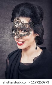 Sensual brunette smiling with retro look and lace mask on black glowing background. The Great Gatsby Movie lookalike concept