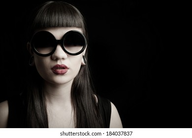 Sensual brunette woman with large red lips wearing  vintage large sunglasses and large earrings and unusual haircut
