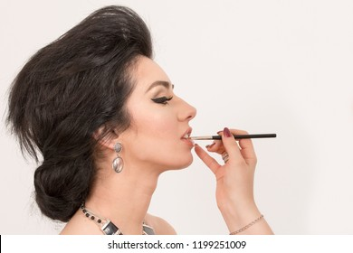 Sensual brunette woman retro styled during makeup lips retouch on white  background. Sophia Loren lookalike concept
