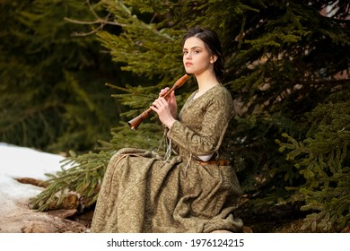 Sensual Caucasian Brunette Female in Old Retro  Medieval Green Dress Playing The Flute Against Firtrees Outdoors. Horizontal Image