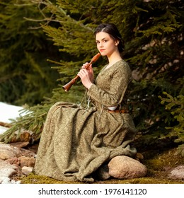 Sensual Caucasian Brunette Female in Old Retro  Medieval Green Dress Playing The Flute Against Firtrees Outdoors. Square Image