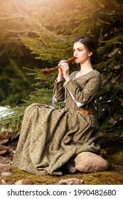 Sensual Caucasian Brunette Female in Old Retro  Medieval Green Dress Playing The Flute Against Firtrees Outdoors. Vertical Orientation