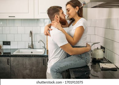 sensual caucasian couple kissing in their home, woman sitting on kitchen table while her husband hugging her. sexy romantic couple in love