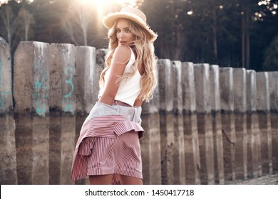 Sensual and charming young blonde girl in a straw hat is posing during walk in the park. Countryside landscape, forest nature at the background. Summertime, summer outside photo