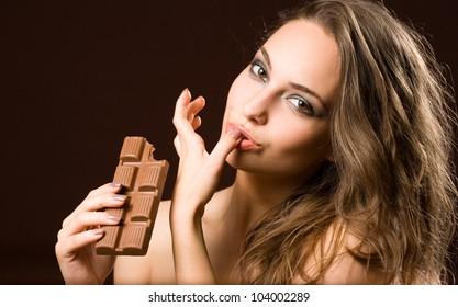 Sensual chocolate fun, young brunette beauty tasting chocolate.