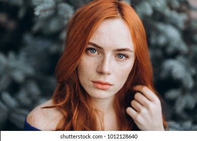 Sensual close up outdoor portrait of a young ginger caucasian attractive girl with freckles dressed in a blue dress. Natural beauty, fashion, emotional concept