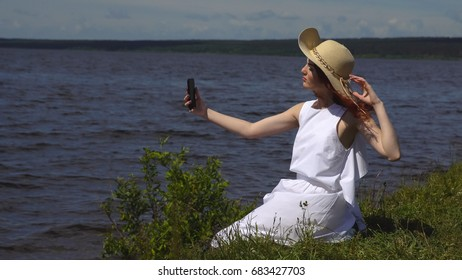 sensual close up portrait of beautiful girl in summer white dress on the river. girl makes a selfie outdoors on a smartphone camera.
