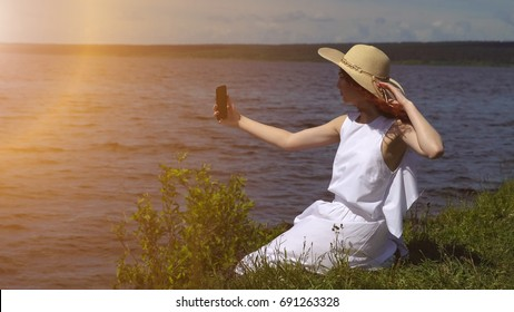 sensual close up portrait of beautiful girl in summer white dress on the river. girl makes a selfie outdoors on a smartphone camera, sunlight