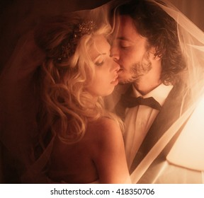 Sensual couple, bride & groom kissing under veil in dark hotel room