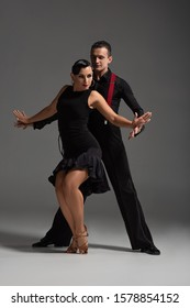 sensual couple of dancers in black, elegant clothing performing tango on grey background
