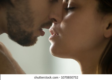 Sensual couple getting closer to feel each others lips, passionate affectionate man and woman enjoying exciting moment of first kiss, intimacy and tenderness in love concept, faces close up side view