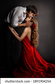 Sensual Couple Kissing in Love. Handsome Man hugging romantic Woman in red Dress. Valentines People Concept