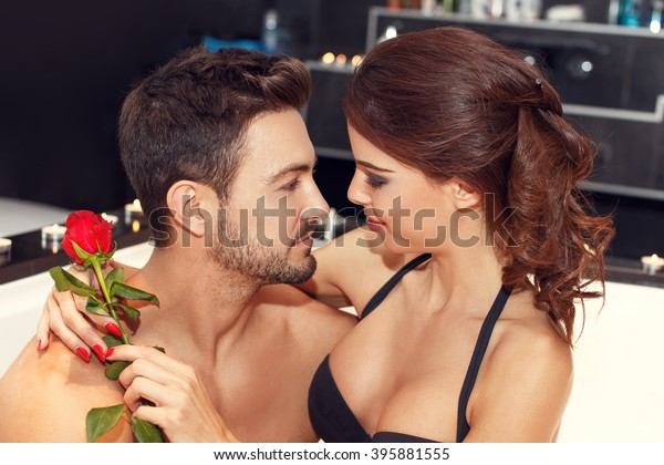 Sensual couple with rose in jacuzzi, looking each other, honeymoon