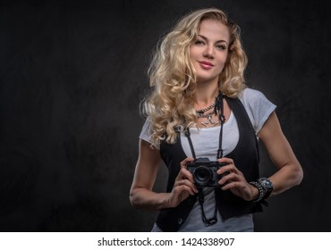 Sensual curly blonde girl photographer dressed in a white t-shirt and waistcoat wears a lot of accessories and wristwatch, posing with a camera at a studio. Isolated on dark textured background.