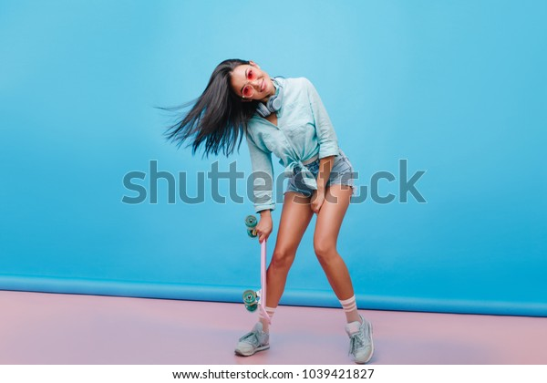 Sensual dark-haired girl in casual street outfit dancing on blue background, holding longboard. Catching hispanic woman in sneakers  posing with smile in studio.