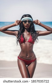 Sensual ebony model in a red bikini, stylish transparent cap and a chain on the belly poses on a tropical beach. Summer fashion