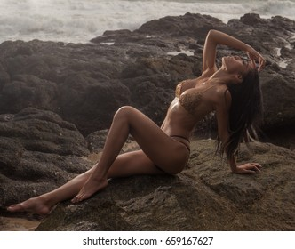 Sensual and elegant brunette beauty wearing gold jewelry bra and black bikini bottom posing on the beach near the rocks over beautiful sea background