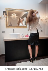 Sensual elegant woman in office outfit looking into a large mirror. Beautiful and sexy blonde young woman wearing an elegant white jacket and a black midi skirt posing in a mirror. Fashionable model.